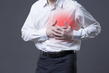 Heart attack, man with chest pain on gray background