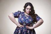 Plus-Size-Modell in lässiger Kleidung, dicke Frau auf beigem Hintergrund, übergewichtiger weiblicher Körper