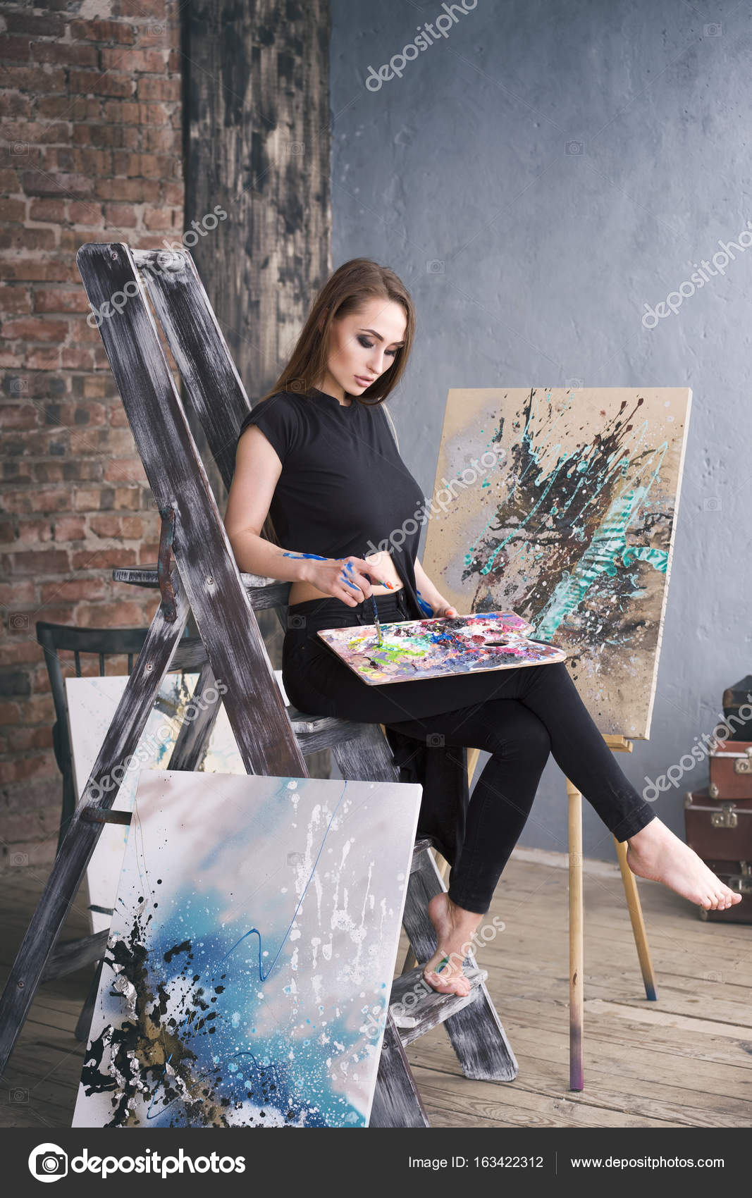 Young Female Artist Painting Abstract Picture In Studio