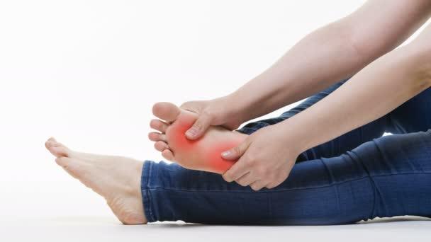 Dolore alle gambe della donna, massaggio dei piedi femminili su sfondo bianco, colpo dello studio
