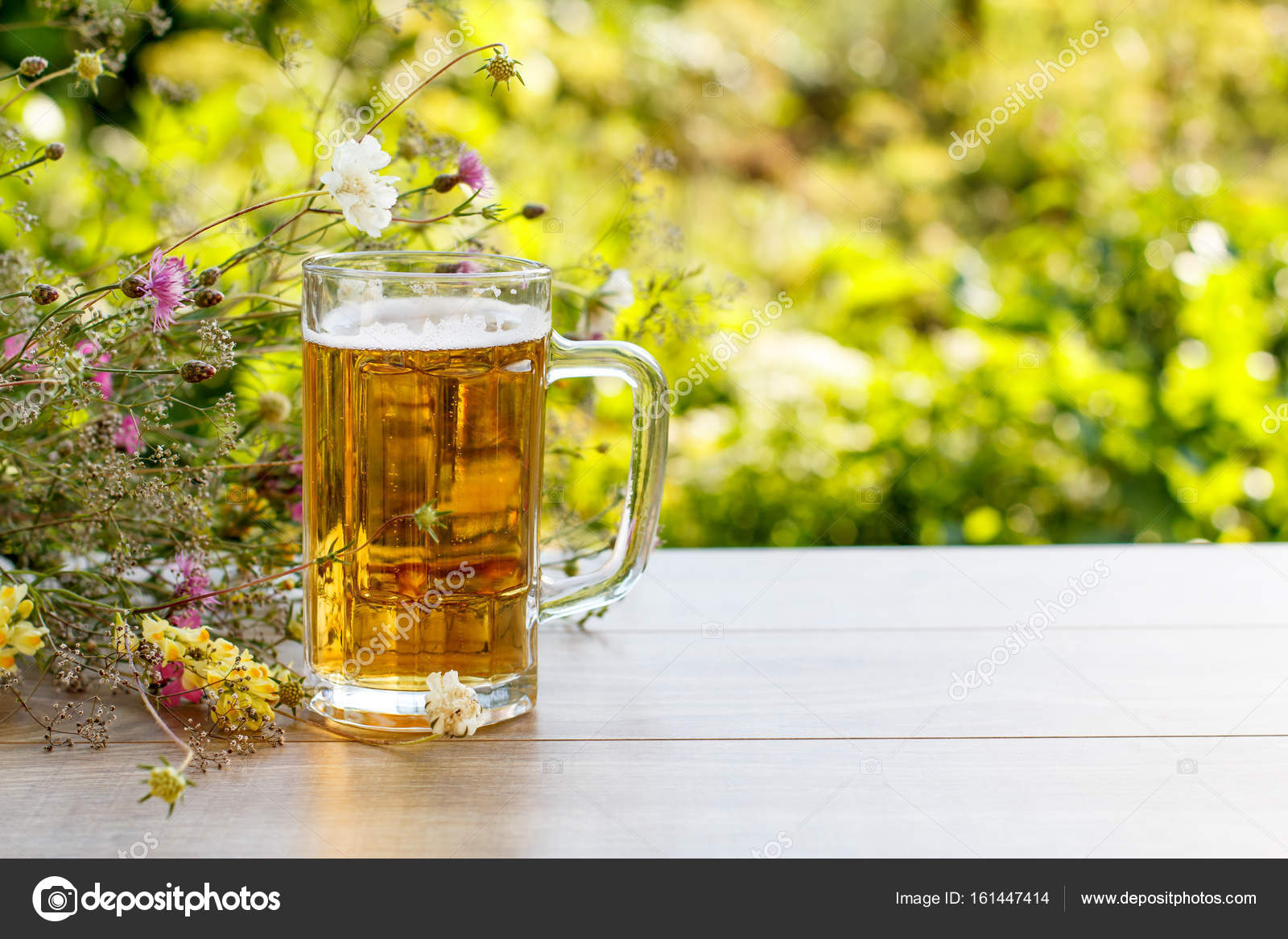 Glass mug of beer on wooden table with bouquet of wildflowers o ...