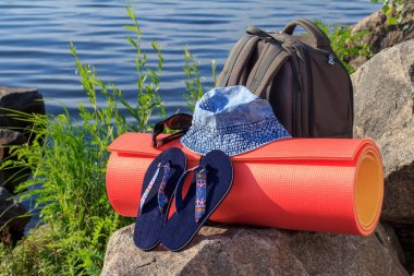 Hiking backpack, hat, flip-flops, sunglasses and camping mat on