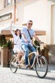 Mladý pár na tandemovém kole na ulici města
