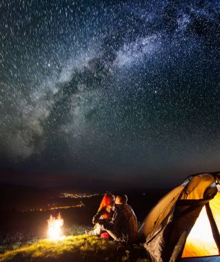 Night camping. Romantic couple hikers sitting and kissing near a campfire and tent under the stars and Milky way. On the background luminous village in the valley
