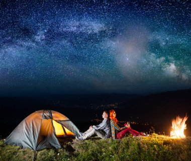 Romantic couple sitting by bonfire near glowing tent