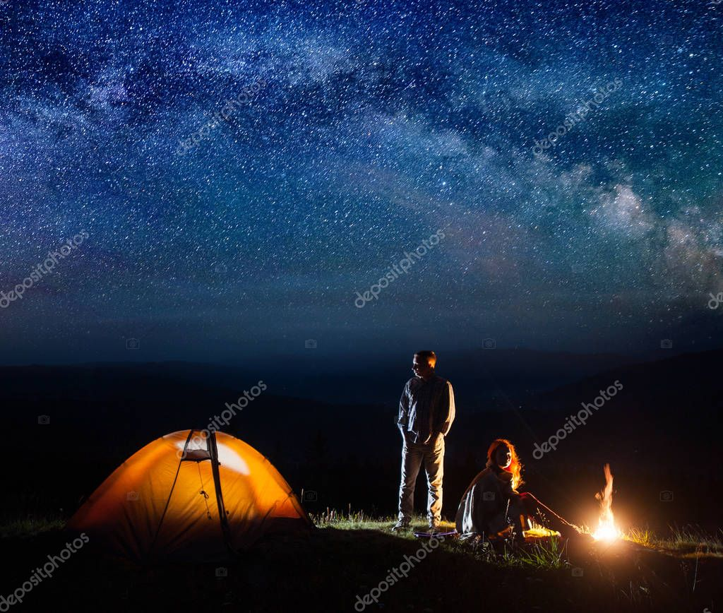 Romantic pair tourists in his camp at night