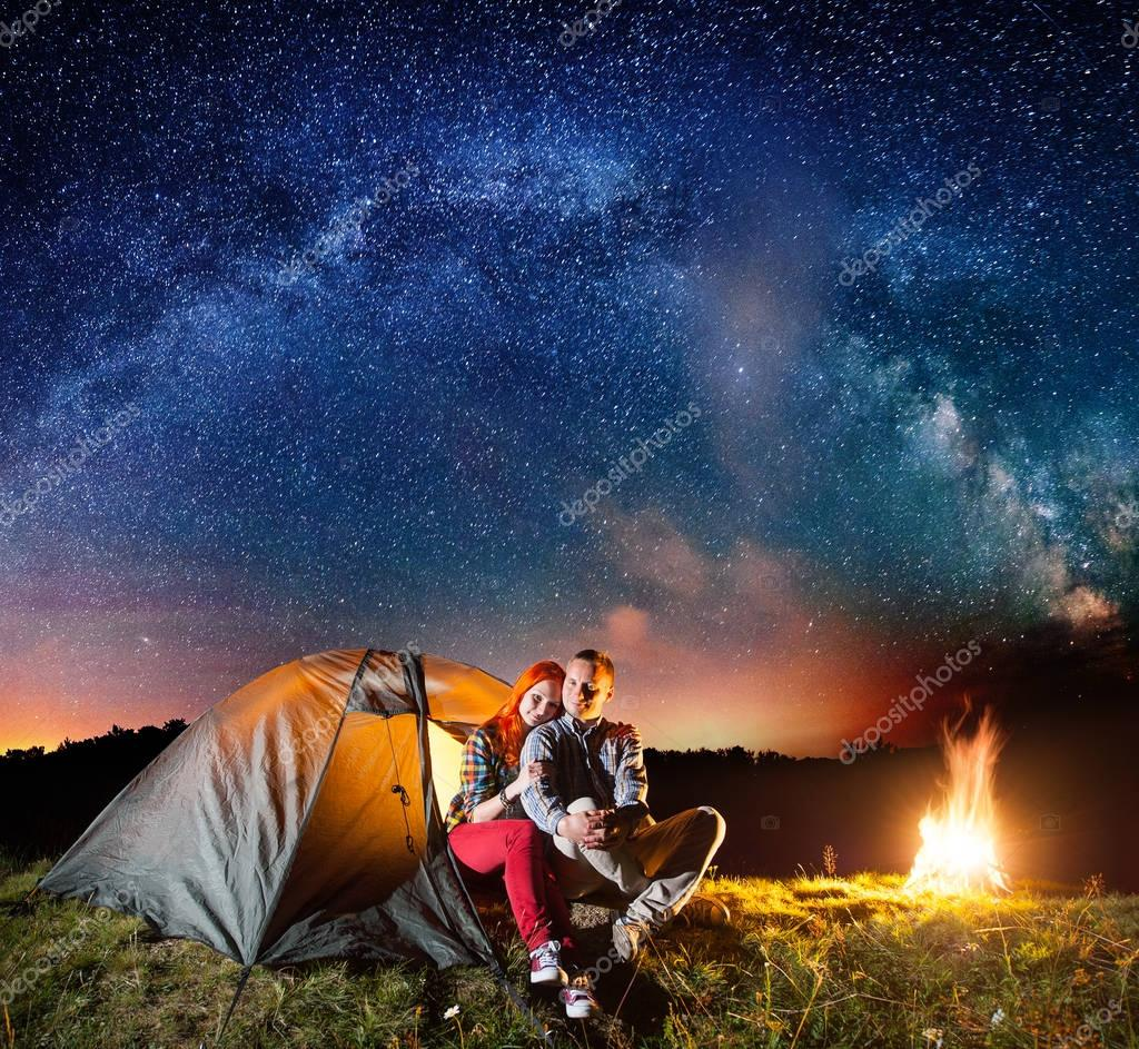 Night camping. Charming couple tourists