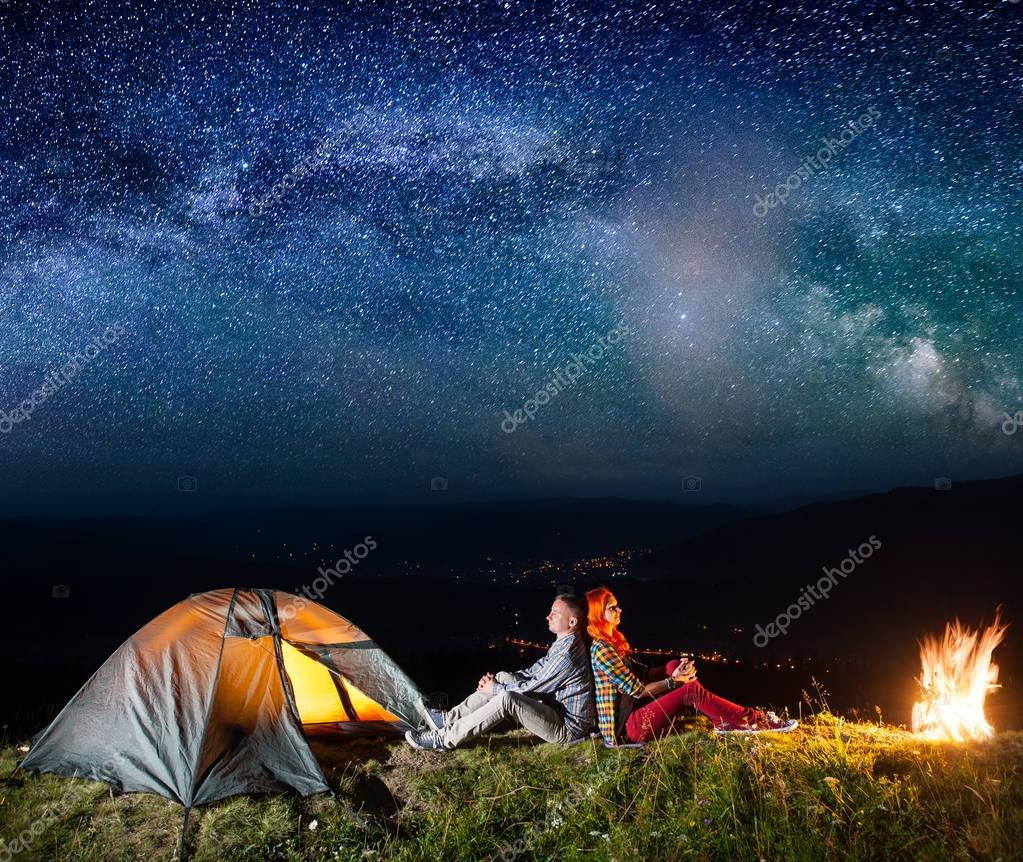 Romantic couple sitting by bonfire near glowing tent