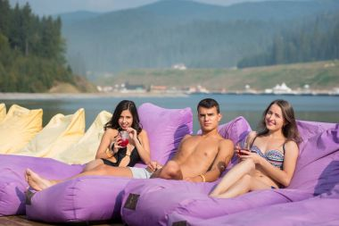 Friends with cocktails on cushioned loungers