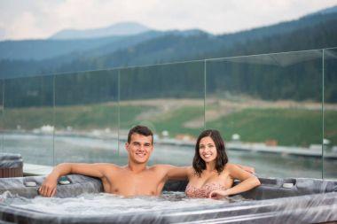 Young couple relaxing enjoying jacuzzi hot tub