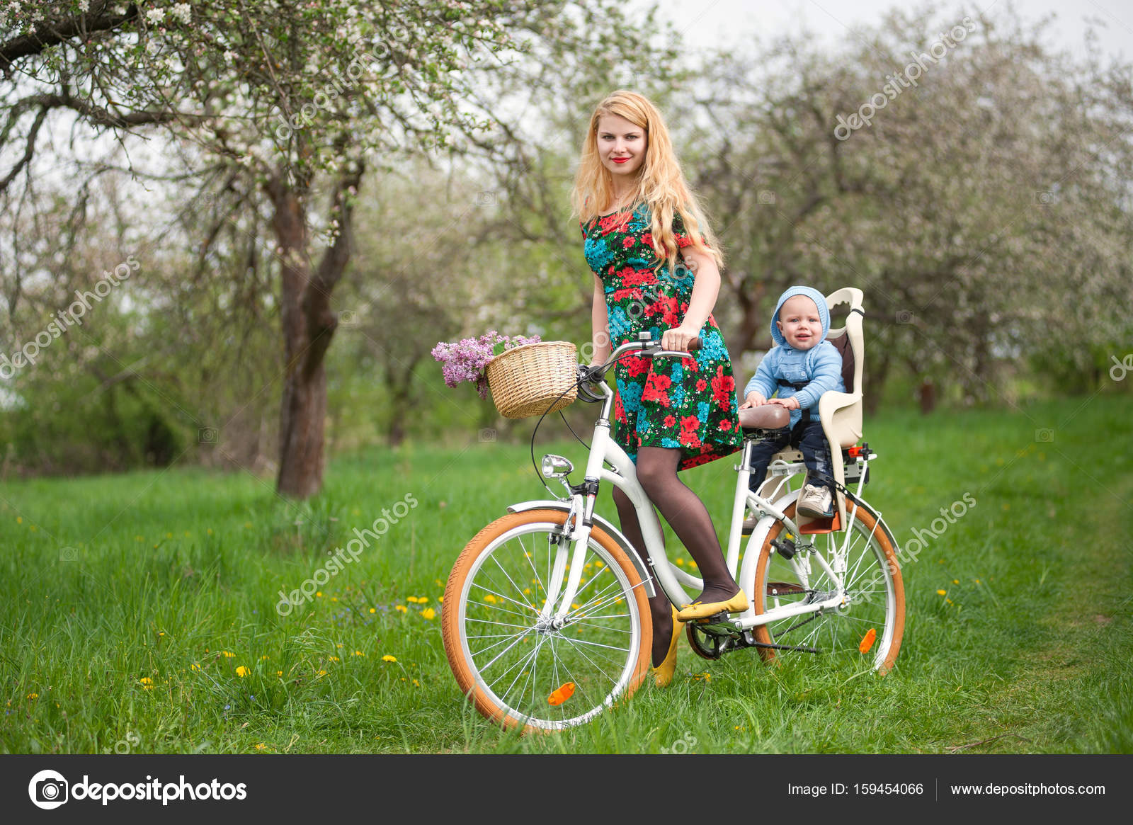 Mother with long blonde hair in dress riding bicycle with baby in bicycle chair. A bouquet of lilacs lay in the basket. Blooming fresh greenery in spring ...  sc 1 st  Depositphotos & Blonde female riding city bicycle with baby in bicycle chair u2014 Stock ...