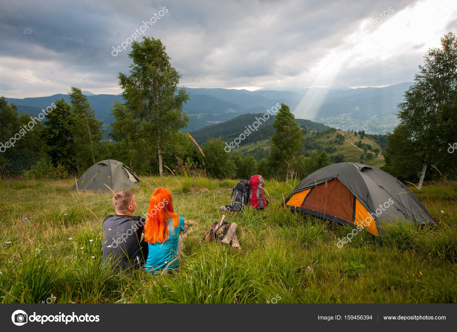 ... green grass near c&fire tents backpacks and looking into the distance on the hills mountains forest and punching the sunu0027s rays through a cloudy ... & Back view of couple sitting on the green grass near campfire ...