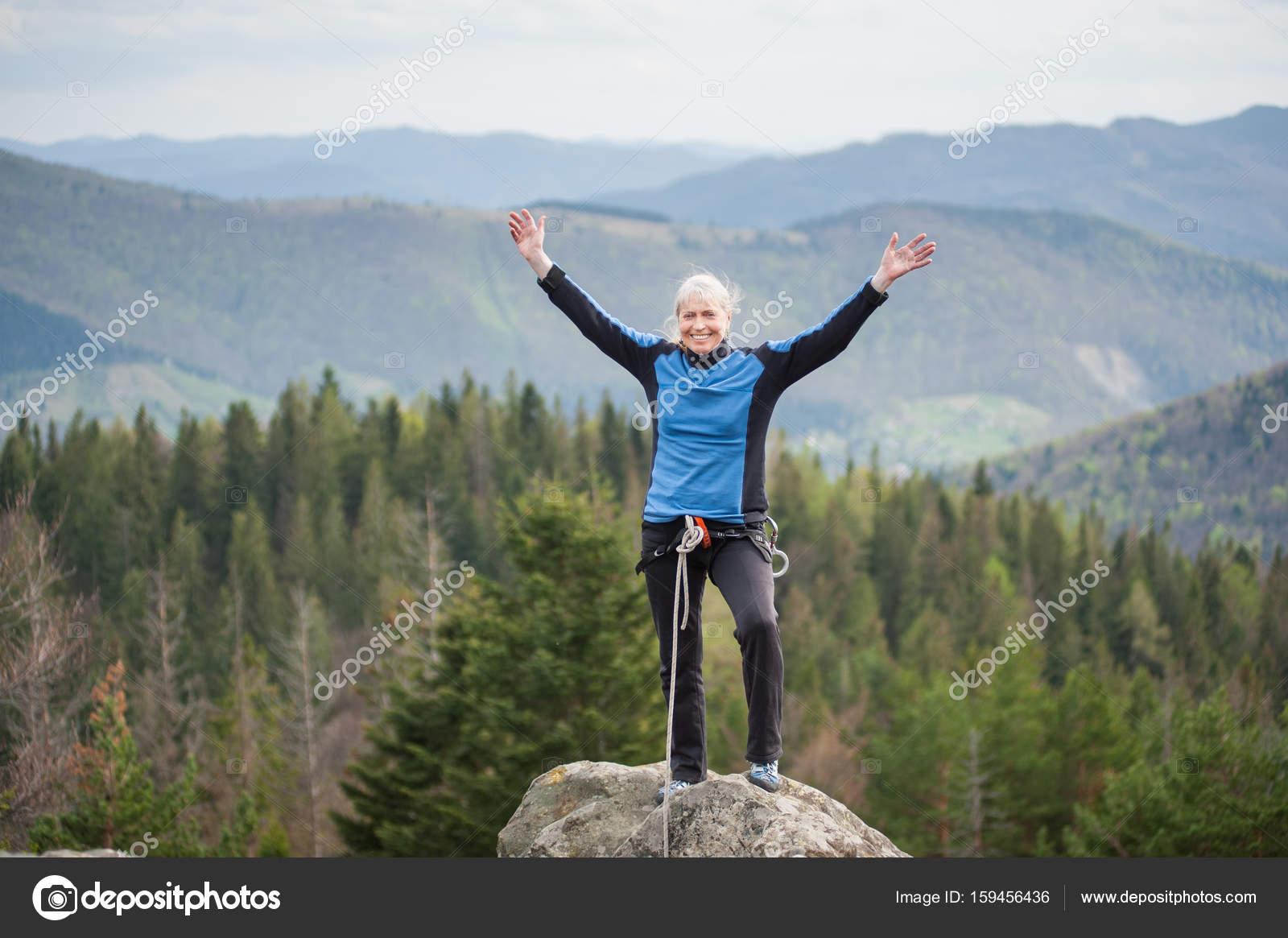 Kletterausrüstung Baum : Weibliche bergsteiger auf dem gipfel des felsens mit