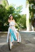 Fotografia donna felice in vestito da estate che propone con bicicletta retrò blu su sfondo di verdi piantagioni di città al giorno pieno di sole
