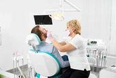 Zahnärztin in Maske mit Spiegel geduldiger Mensch Zähne nachschauen in moderner Zahnklinik Büro