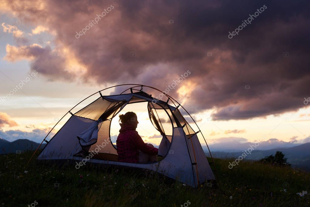 Female tourist sitting in her tent on top of a mountain during stunning sunset copyspace camping hiking travelling tourism lifestyle natural landscape scenery evening relaxation.