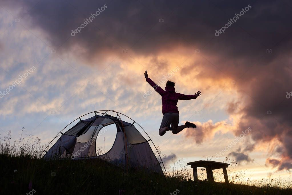 Happy woman jumping high excitedly. Camping in the mountains at sunset copyspace tent campsite recreation weekend nature harmony emotions happiness enjoyment landscape dusk