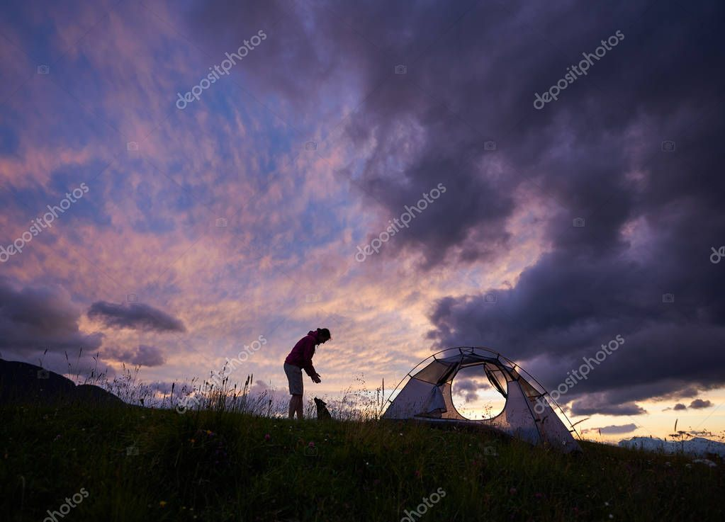 Silhouette of a female traveller playing with small dog near her tent on the mountain top during spectacular sunset copyspace hiking lifestyle camping tourism nature evening landscape.