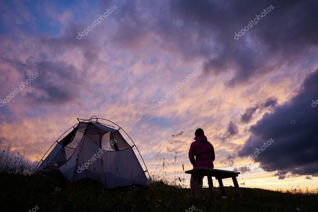 Hiker woman sitting on a bench near a tent and looking at incredible view of sunset evening sky with purple clouds. Young tourist girl alone in cold weather near the campsite outdoors. Travel concept.