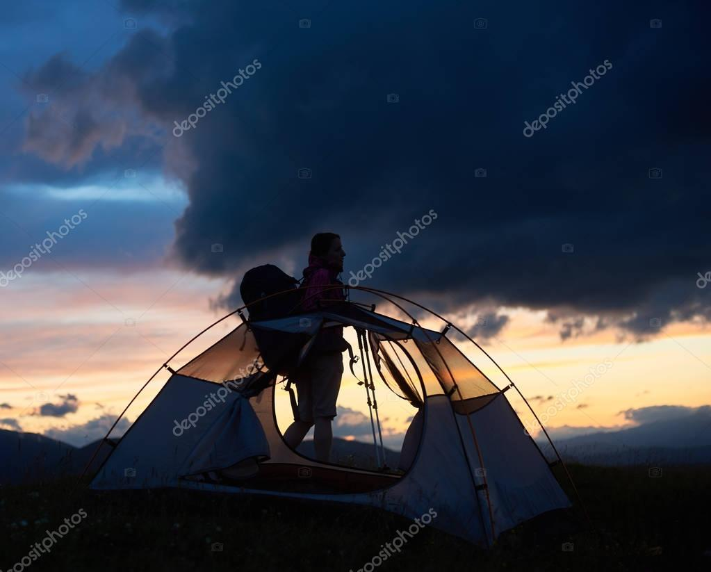 Silhouette of young female tired hiker with trekking sticks and a backpack near tent, sunset time with rising sun in the mountains