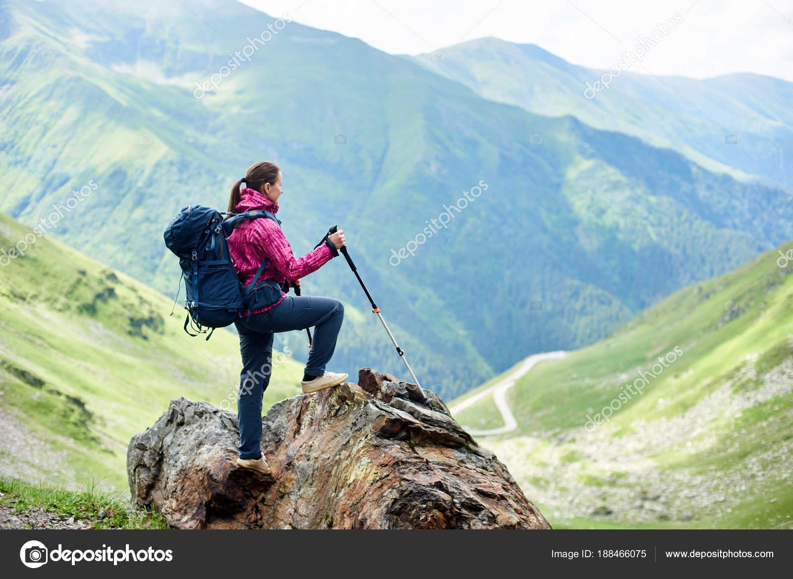 Flickan är stående på toppen av berget och njuter Visa bergen i Rumänien.  Kvinna med ryggsäck och trekking pinnar– stockbild d805ff9452e49