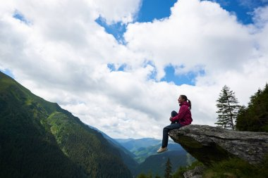 Profile of the girl sitting on the rock, dangling her legs in the abyss against the backdrop of green mountains with forests and clouds above them through which the blue sky is visible.