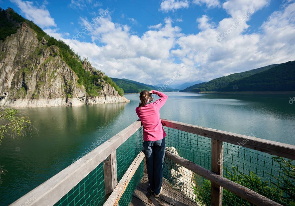 Rear view of female photographer on the lake Vidraru Carpathians Romania. Beautiful scenery of a sunny day: mountains, forests, lake, blue sky with clouds