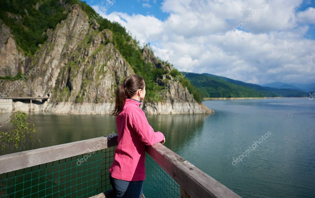 Brunette female tourist looking far into the distance admiring magnificent views of green rocky mountains and breathtaking Vidraru lake in Romania. Woman amazing beautiful scenery landscape happy calm