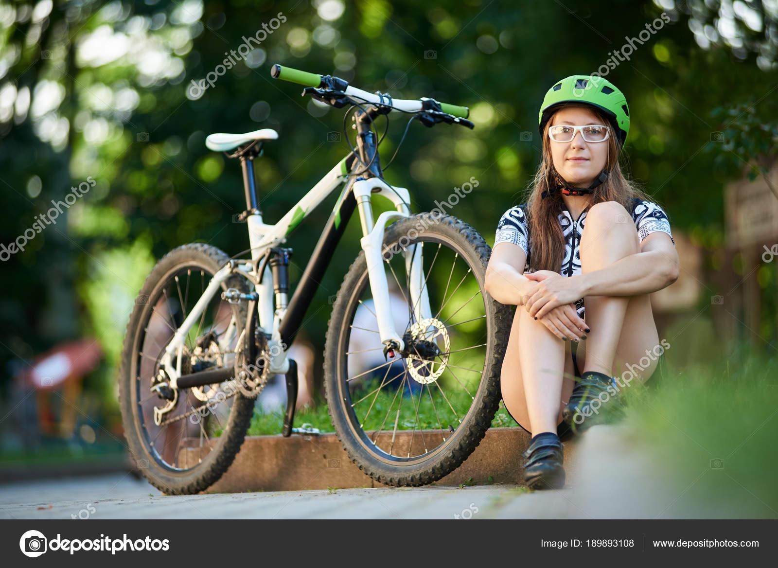 Γυναίκα ποδηλάτης επαγγελματική ποδηλασία ρούχα και κράνος κάθεται κοντά  ποδήλατο στην άκρη του δρόμου σε ηλιόλουστο da9261e4631