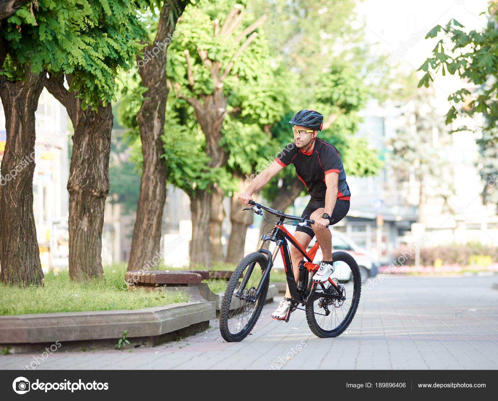 Αθλητικός τύπος ποδηλάτη στην ποδηλασία ρούχα και προστατευτικό εξοπλισμό  ιππασίας με ποδήλατο κατά μήκος το άδειο πόλη δρόμους dc409d1df66