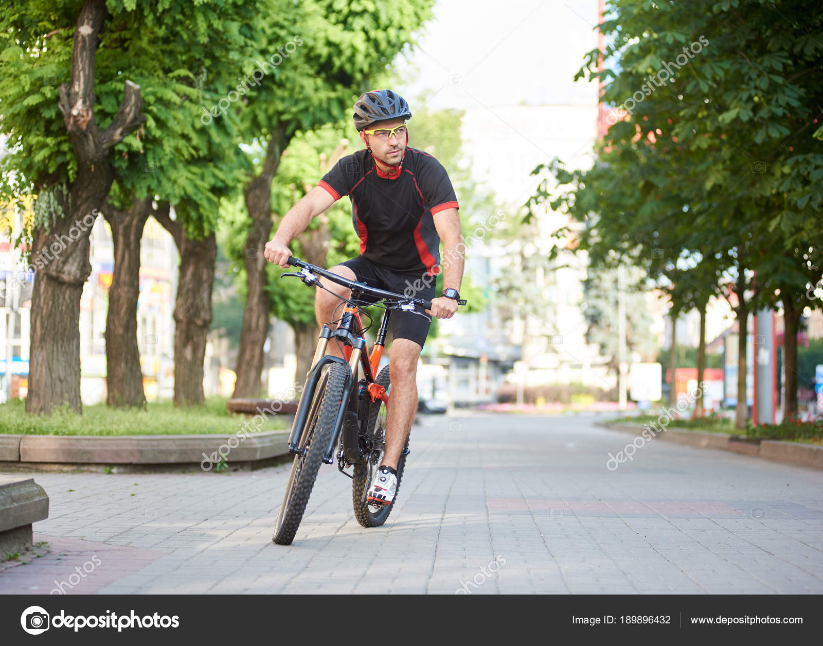 Man Professional Biker Riding Bicycle Empty City Streets Green Trees