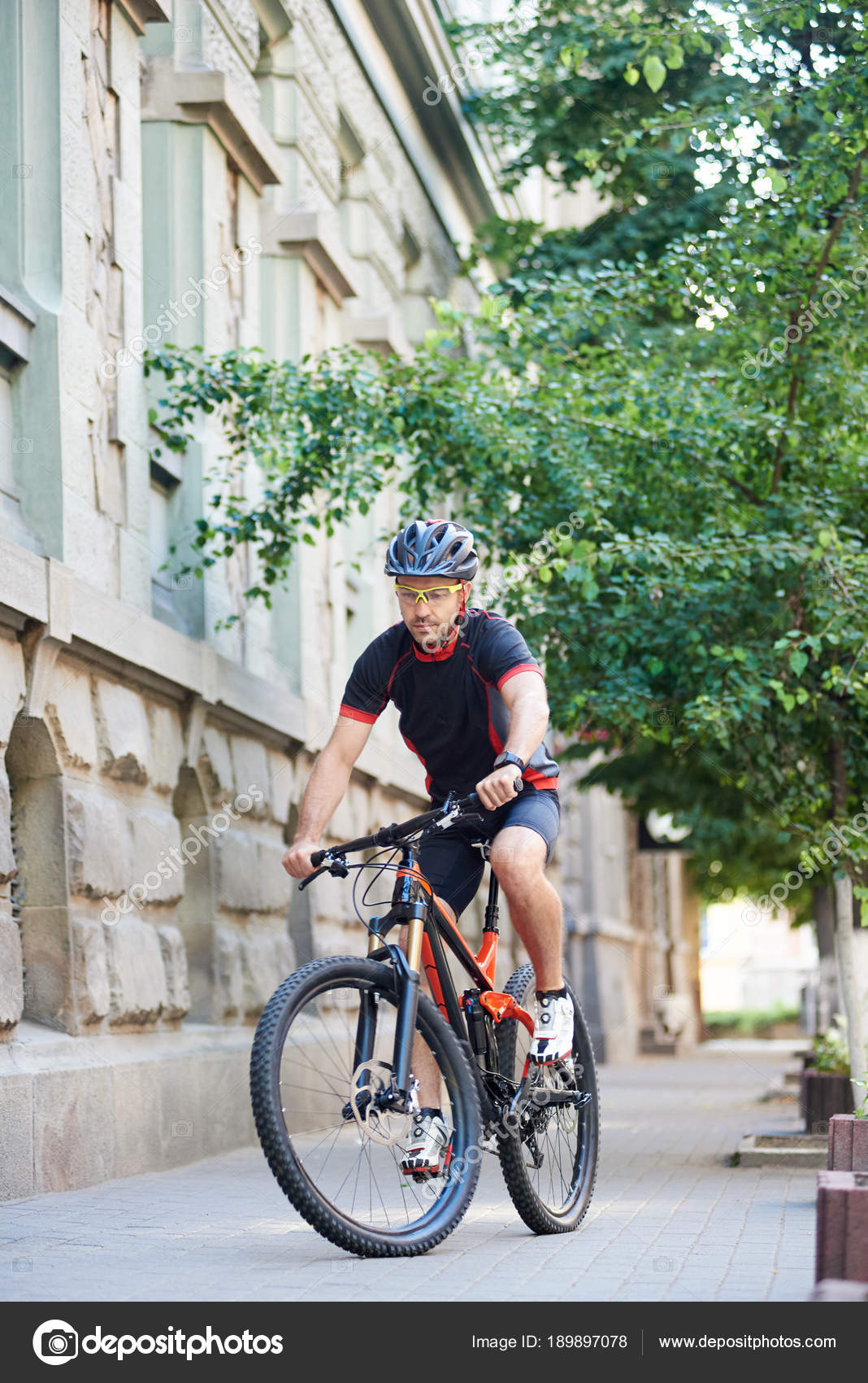 Athletic man bicyclist wearing professional cycling clothing and helmet  doing extreme sports on bicycle in old city streets. Sportsman training in  urban ... 2495d16c9