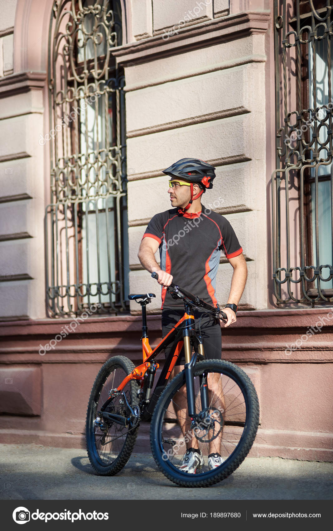 Athletic man cyclist in professional cycling clothing and protective helmet  standing near old historical building next to bicycle looking in distance  and ... c60bcde02