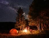 Fotografie Skupina čtyři přátelé turisty oteplování své ruce kolem táborového ohně, oddechuje poblíž zářící oranžové stan za neobvykle hvězdnou oblohu a mléčné dráhy v noci