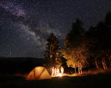Group of tourists at night camping near the forest at the illuminated tent, looking at the burning fire under incredible beautiful starry sky and Milky way on the background of mountains and hills.