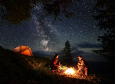 Romantic male and female tourists warming themselves around the fire at night. Camping in the mountains near the trees and illuminated orange tent.