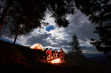 Four person tourists are sitting around a campfire with a beer near the camping and forest at night in the mountains. Blue sky is visible through the clouds.