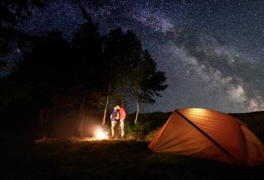 Guy and girl hikers having a rest by the campfire under a bright starry sky which is visible Milky way near the orange tent and trees.