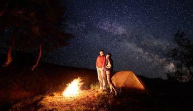Young couple man and woman hikers smiling to each other, standing near campfire and orange tent during night camping under starry sky and Milky way.