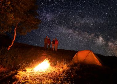 Group of hikers enjoying the unusual sky strewn with bright stars during the night camping. In the foreground, a fire burns near the tent and the trees.