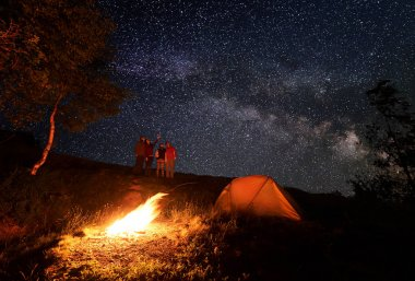 Four person enjoying the unusual sky strewn with bright stars during the night camping. Girl shows the rest of the group up on Milky way.