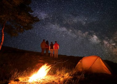 Rear view of a group of hikers enjoying the starry sky which is visible the Milky way during a night of camping near a campfire and orange tent.