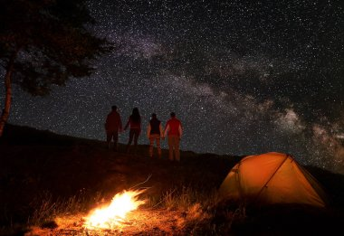 Back view of two couples of hikers holding hands and enjoying milky way at starry sky during a night of camping near a campfire and orange tent in mountains.