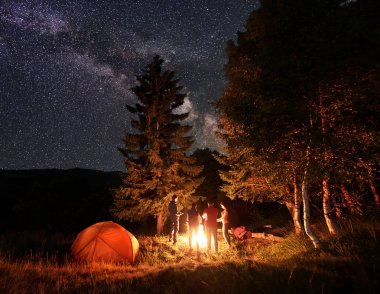 Group of four friends hikers warming their hands around a campfire, having a rest near glowing orange tent under unusually starry sky and Milky way at night.