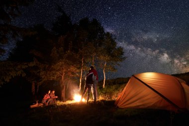 Tourists during a night in camping around a campfire near orange tent. One pair is hugging each other, the second pair is sitting on a log under the starry sky and Milky way on a background of trees