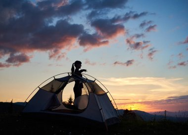 Silhouette of girl standing in profile near tent, shows her hand in the distance under morning sky at daybreak with incredible landscape of mountains and the rising sun above them. View through a tent