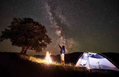 Back view woman tourist having a rest at night camping in mountains. Female hiker standing beside campfire and illuminated tent near big tree, pointing at incredible beautiful starry sky and Milky way