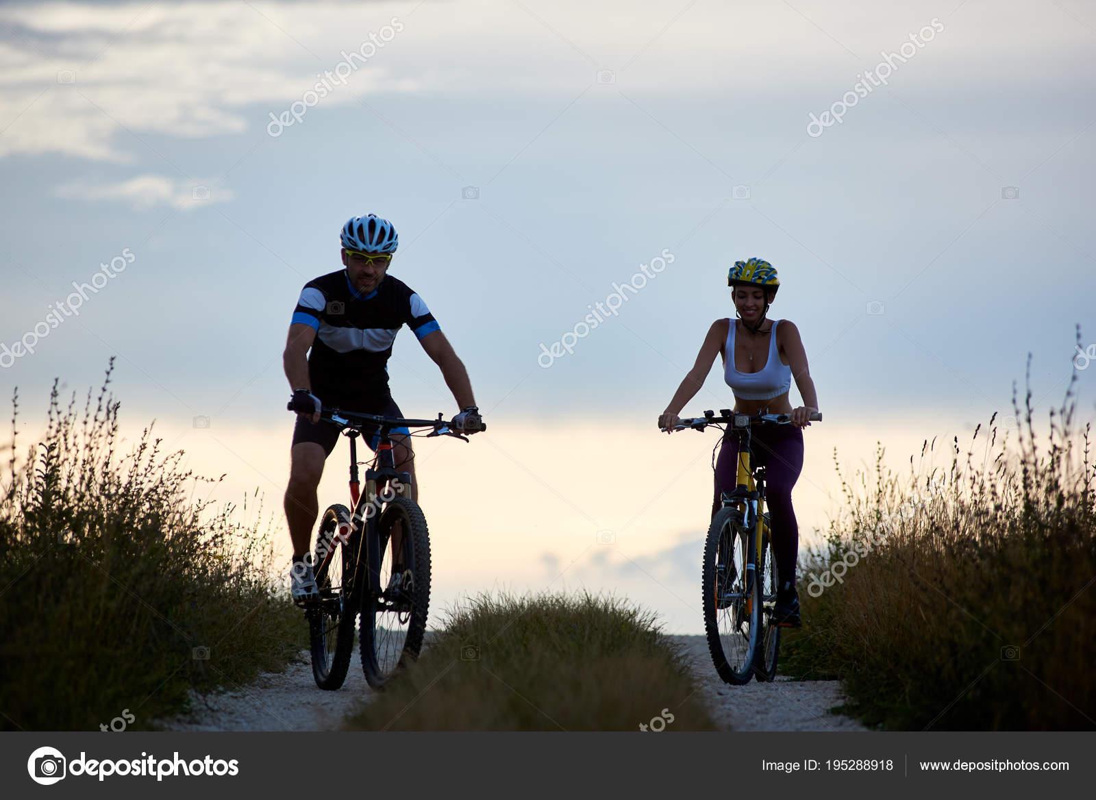 Ζευγάρι του ποδηλάτη ιππασία ποδήλατα σε επαρχιακό δρόμο. Ταιριάζει νέους  ανθρώπους σε αθλητικά ρούχα ποδηλασίας κατάβασης ενάντια όμορφο ορίζοντα με  τέλειο ... 15090023dfc