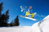 Snowboarder Mann mit Brille und Helm fährt Snowboard schnell den steilen, schneebedeckten Berghang hinunter vor blauem Himmel und Fichten an sonnigen Wintertagen