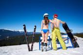 Zadní pohled na ženu v plavkách s lyžemi a muže nahoře bez se snowboardem těší pohled na zasněžené hory